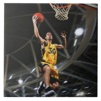 空気で跳んでいるバスケットボール選手 タイル