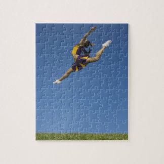 空気で高く跳躍しているメスのチアリーダー ジグソーパズル