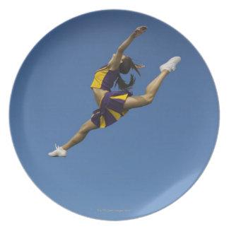 空気で高く跳躍しているメスのチアリーダー プレート