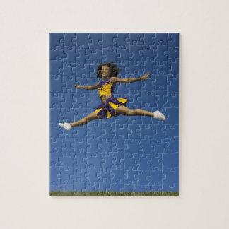 空気のジャンプの割れ目をしているメスのチアリーダー ジグソーパズル