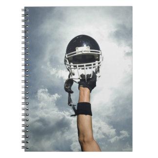空気のヘルメットを握っているフットボール選手 ノートブック