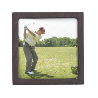 範囲で練習の球に当っている年長のゴルファー ギフトボックス