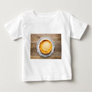 素朴な木製のケーキの上のチーズケーキ ベビーTシャツ