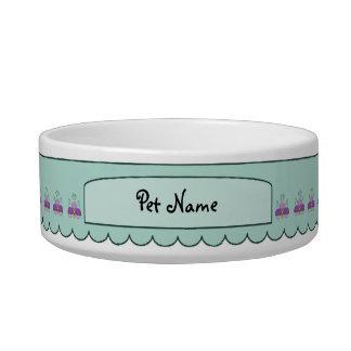 紫色および青緑色の曇らされたカップケーキを持つかわいいモンスター ボウル