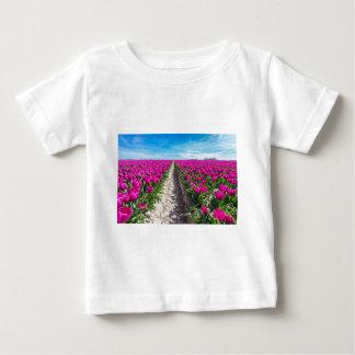 紫色のチューリップおよび道が付いている花分野 ベビーTシャツ
