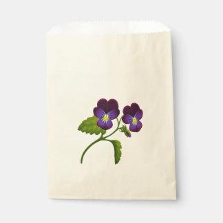 紫色の庭のパンジーによっては好意のバッグが開花します フェイバーバッグ