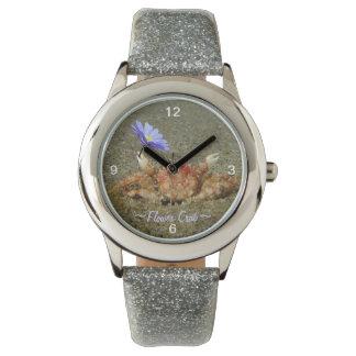 紫色の花の腕時計を握っているベビーのカニ 腕時計