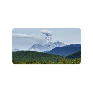 絵のような火山噴火および緑の森林 ラベル