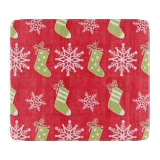 緑のクリスマスのストッキングおよび雪片 カッティングボード