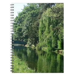 緑の明るい春日の緑の木の川の歩行 ノートブック