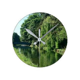 緑の明るい春日の緑の木の川の歩行 ラウンド壁時計