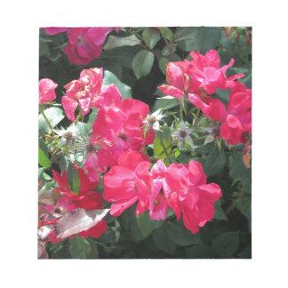 緑の背景が付いている赤い花 ノートパッド