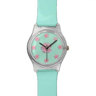 緑の背景の腕時計のピンクのバラ 腕時計