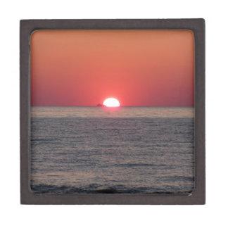 背景の貨物船との暖かい海の日没 ギフトボックス
