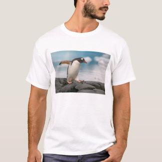 背景幕3が付いている岩が多い海岸線のGentooのペンギン Tシャツ