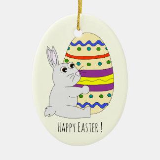 色彩の鮮やかな卵の子供を握るかわいいイースターのウサギ セラミックオーナメント