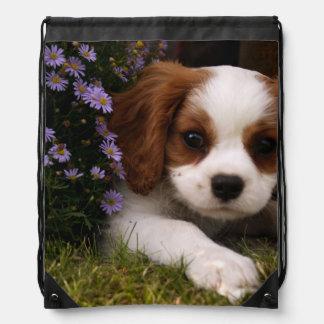 花の後ろの無頓着なチャールズ王スパニエル犬の子犬 ナップサック