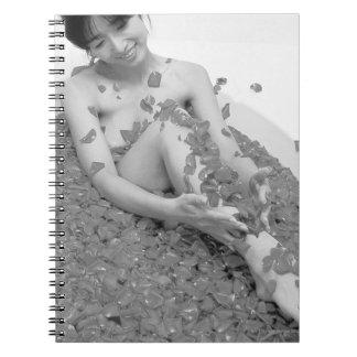 花の花びらを搭載する温水浴槽でリラックスしている女性 ノートブック