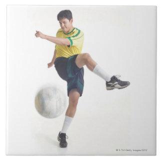 若いラテン系の男性は黄色いサッカーjerseyを身に着けています タイル