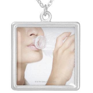若い女性の飲料水、クローズアップ シルバープレートネックレス