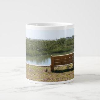 草および水が付いている川によるベンチ ジャンボコーヒーマグカップ