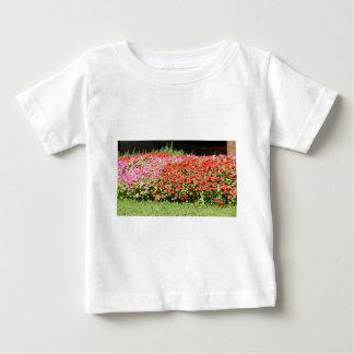 草の隣のピンク及び赤い花の花園 ベビーTシャツ