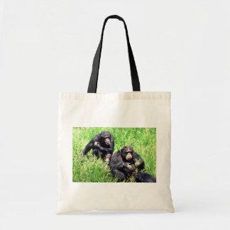 草(ノートの乳児)を食べているチンパンジー トートバッグ