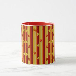 葉のコンボのマグが付いている赤および黄色のストライプ マグカップ