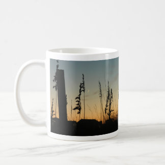 薄暗がりのビーチの草そして家 コーヒーマグカップ