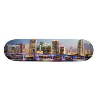 薄暗がりの都心のマイアミの照らされたスカイライン スケートボード