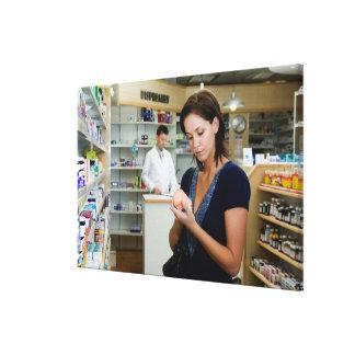 薬学の薬を見ている若い女性 キャンバスプリント