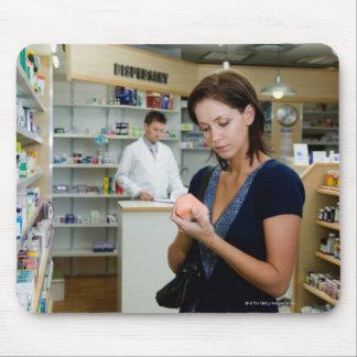 薬学の薬を見ている若い女性 マウスパッド