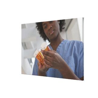 薬瓶を点検しているジャマイカのメスのナース キャンバスプリント