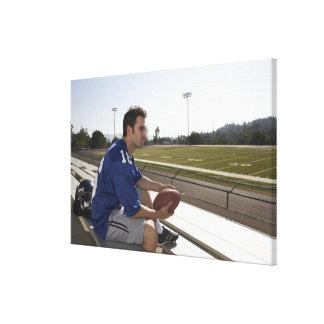 観覧席に坐っているアメリカン・フットボールプレーヤー キャンバスプリント