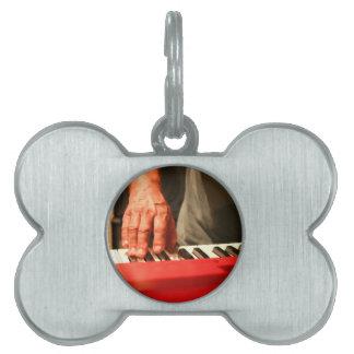 赤いキーボードの男性のミュージシャンを演じる手 ペットネームタグ