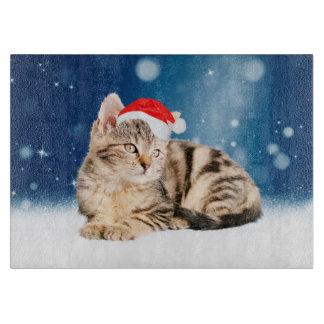 赤いサンタの帽子のクリスマスの雪を身に着けているかわいい猫 カッティングボード