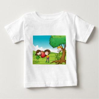 赤いハートを握っている女の子および男の子 ベビーTシャツ