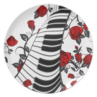 赤いバラおよびピアノ鍵は、つかまえを注目します! プレート
