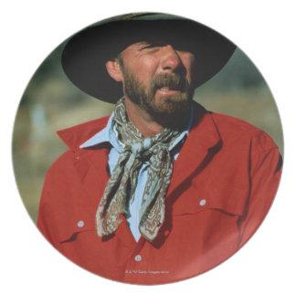 赤いワイシャツを身に着けている馬に坐っているカウボーイ プレート