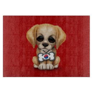 赤い韓国の旗のドッグタッグを持つかわいい子犬 カッティングボード