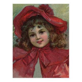 赤くビクトリアンな服を持つヴィンテージのクリスマスの子供 ポストカード