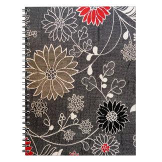 赤く、茶色、白い花が付いている模造のな花の織物 ノートブック