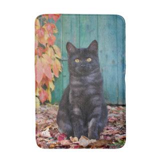 赤のかわいい黒猫の子ネコは青いドアを去ります- バスマット