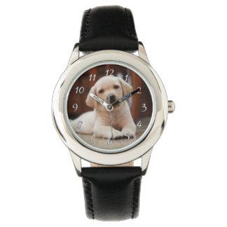赤ん坊の腹に置いている黄色いラブラドールの小犬 腕時計