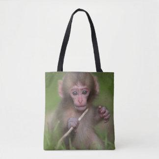 赤ん坊猿は小枝によって遊んでいます トートバッグ