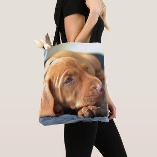 足で休んでいるVizslaの子犬 トートバッグ