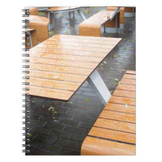 通りのぬれた屋外のカフェのテーブル ノートブック