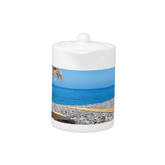 道が付いているビーチパラソルおよび海岸の石