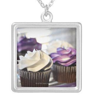 選択的な焦点が付いているカップケーキのクローズアップ シルバープレートネックレス
