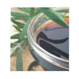 醤油およびローズマリーの葉が付いているガラスコップは閉まります ノートパッド
